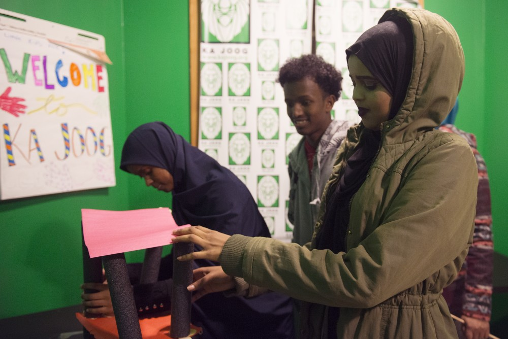 Zainab Mohamed, Myrdal Muse and Suhur Mohamud set up a tower for an experiment at the Ka Joog mentorship program in Riverside Mall on Nov. 5, 2016.