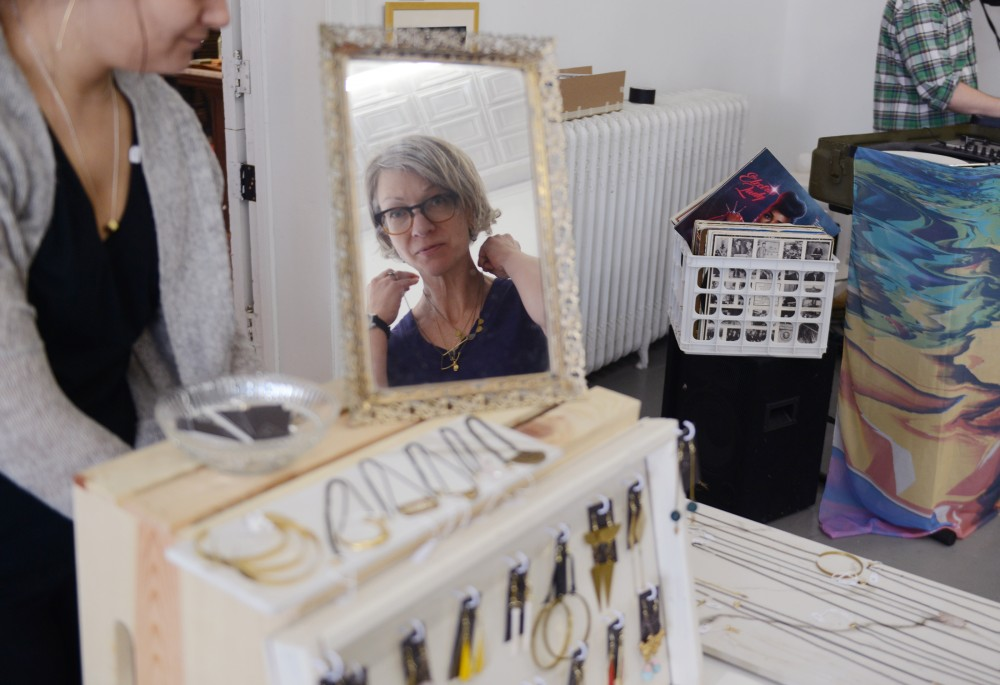 Ceramist Stephanie DeArmond tries on a necklace made by Tess Weinberg of Belle Isle Design Co on Saturday, Dec. 3, 2016 at The White Page art gallery. The White Page hosted its 3rd artist market with 23 local artists over the weekend.
