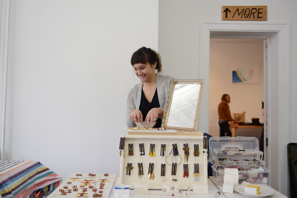 Jewelry designer Tess Weinberg of Belle Isle Design Co lays out jewelry on Saturday, Dec. 3, 2016 at The White Page art gallery.