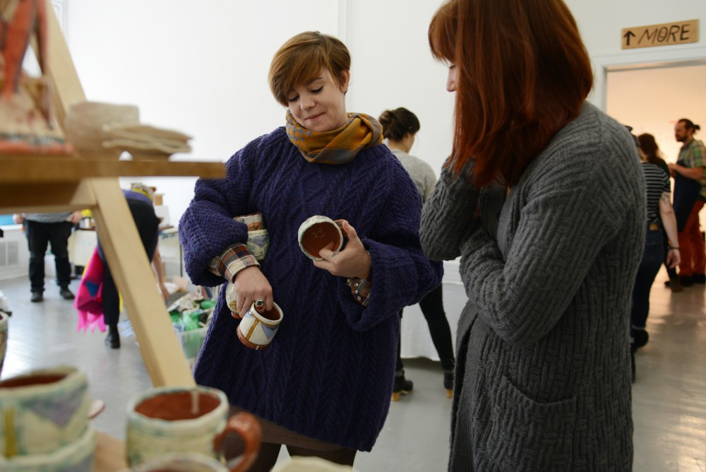Ceramist Amanda Dobbratz talks with ceramist Erin Paradis while setting up her table on Saturday, Dec. 3, 2016 at The White Page art gallery.