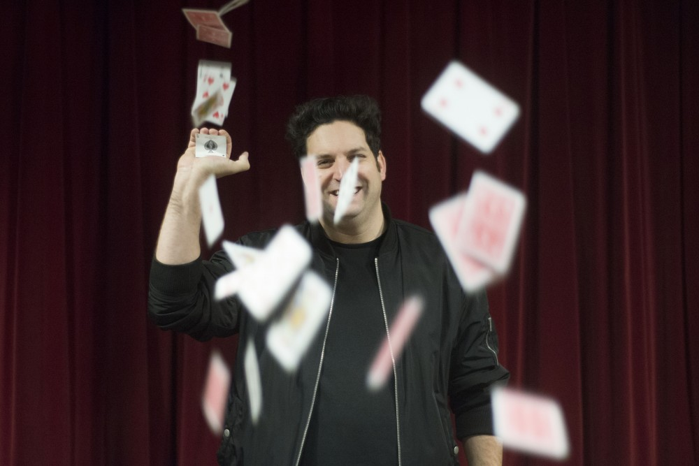 Cards rain on magian David Harris as he poses for a portrait at Bryant-Lake Bowl and Theater on Friday, Dec. 9, 2016.
