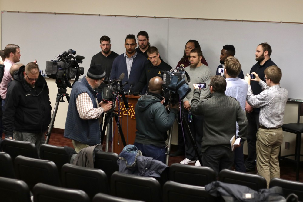 Gopher football players surround senior wide receiver Drew Wolitarsky, center, as he addresses reporters at a news conference on Saturday, Dec. 17, 2016. The team announced the end of the Gophers football team's boycott.