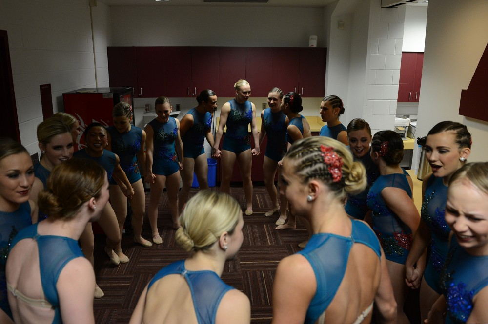 University of Minnesota Dance Team circles up and holds hands in their costumes as play their jazz music to prepare and energize prior to their performance at the Spirit Squad Nationals Send Off on Monday, Jan. 9, 2017.
