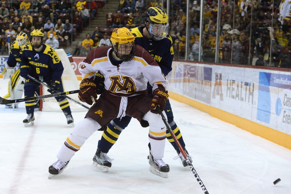 Gophers forward Vinni Lettieri chases the puck into the corner against Michigan on Friday, Jan. 13, 2017 at Mariucci Arena.