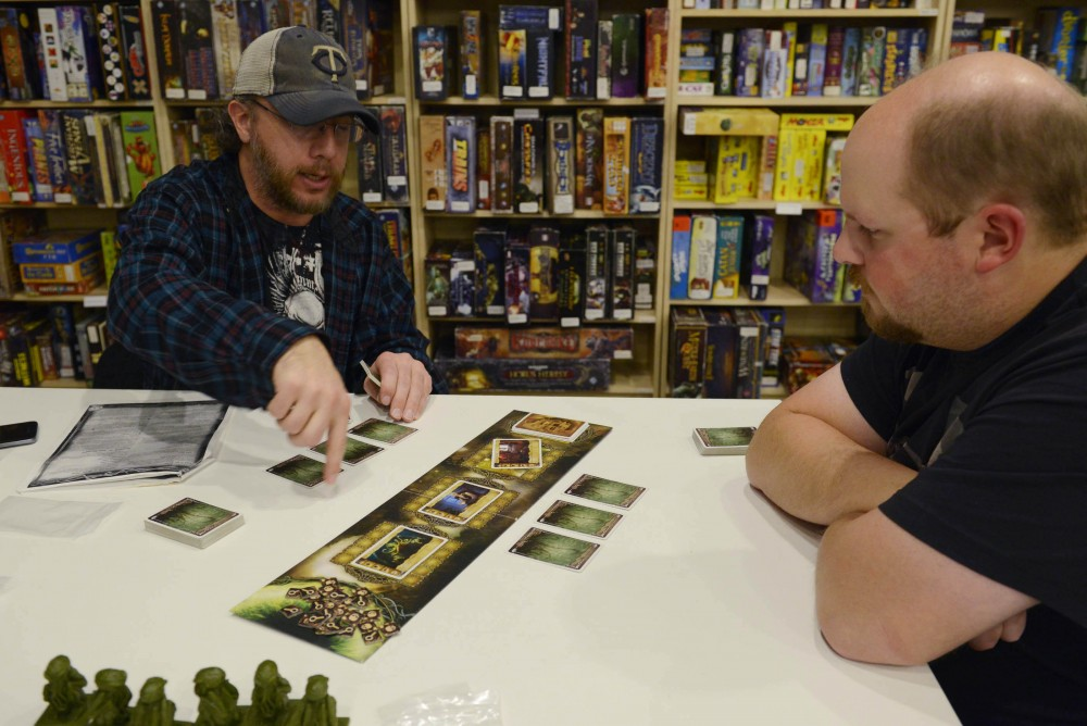 Rob Schleicher explains the game Call of Cthulhu to Ryan Albright as both learn how to play it at Fantasy Flight Games in Roseville on Jan. 16, 2016. The center hosts a variety of activities and competitions for tabletop game enthusiasts in the Twin Cities.