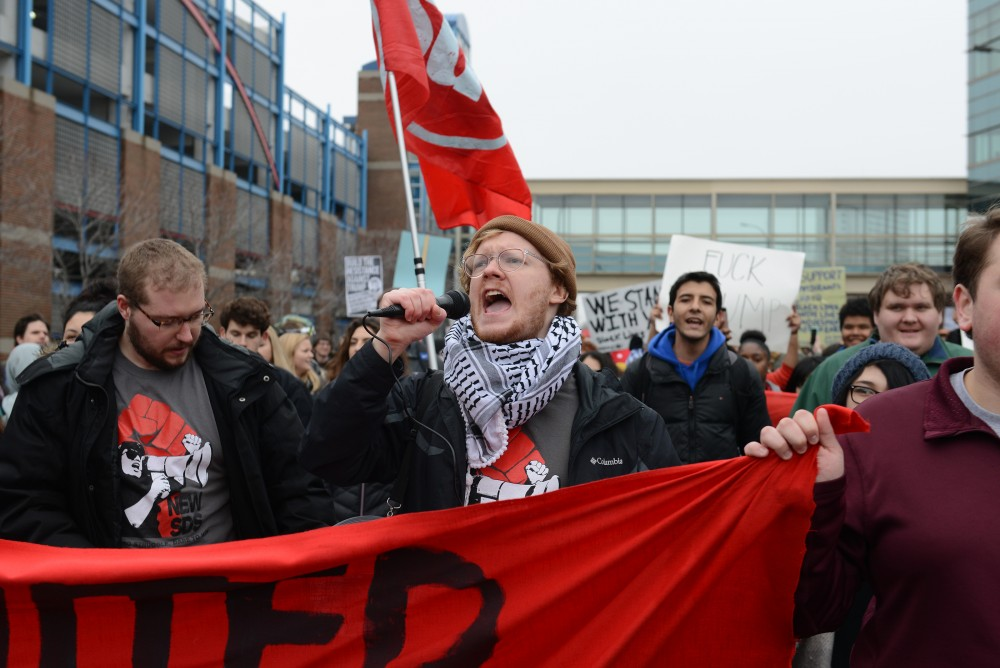 Students For a Democratic Society Organizer Skyler Dorr leads protesters ina chant against President Donald Trump on 19th Avenue South on Friday, Jan. 20, 2017. Students gathered outside the Humphrey School of Public Affairs and marched to City Hall, joining with groups from other colleges and communities along the way.