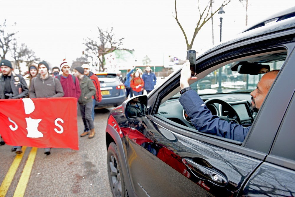Onlooker Santiago Bermudez takes a video from his car as protesters disrupt traffic on Cedar Avenue on Friday, Jan. 20, 2017.