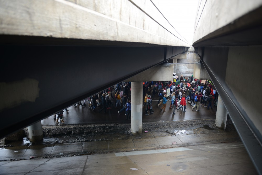 Protesters pass under Interstate 94 on Cedar Avenue to speak out against President Donald Trump on Friday, Jan. 20, 2017. Students gathered outside the Humphrey School of Public Affairs and marched to City Hall, joining with groups from other colleges and communities along the way.