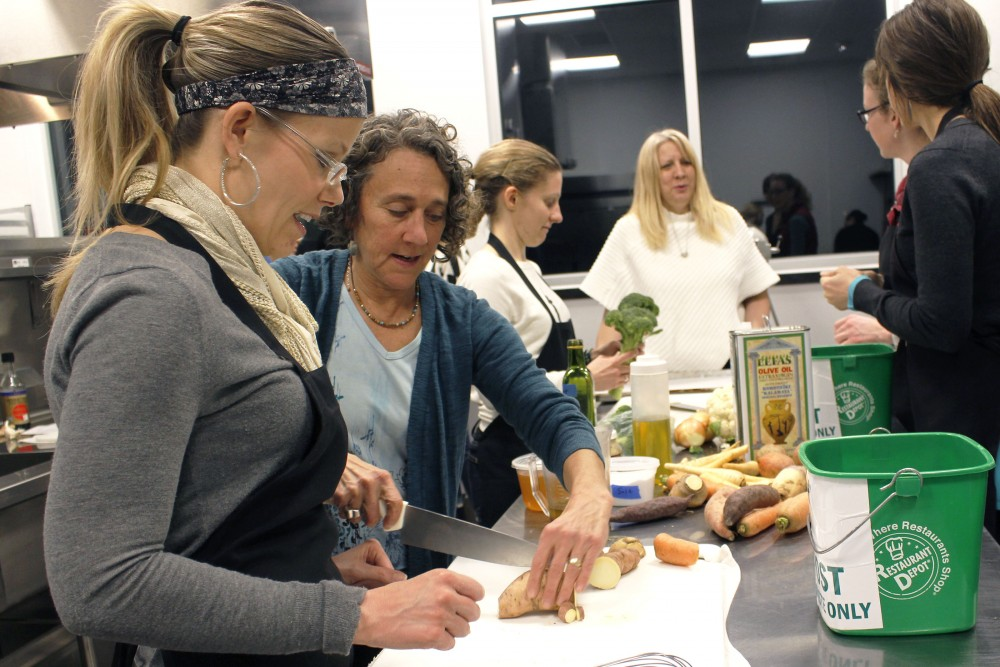 Professional chef Jenny Breen helps Katelyn Erickson cut a sweet potato at The Good Acre in St. Paul on Wednesday, Jan. 17, 2017.