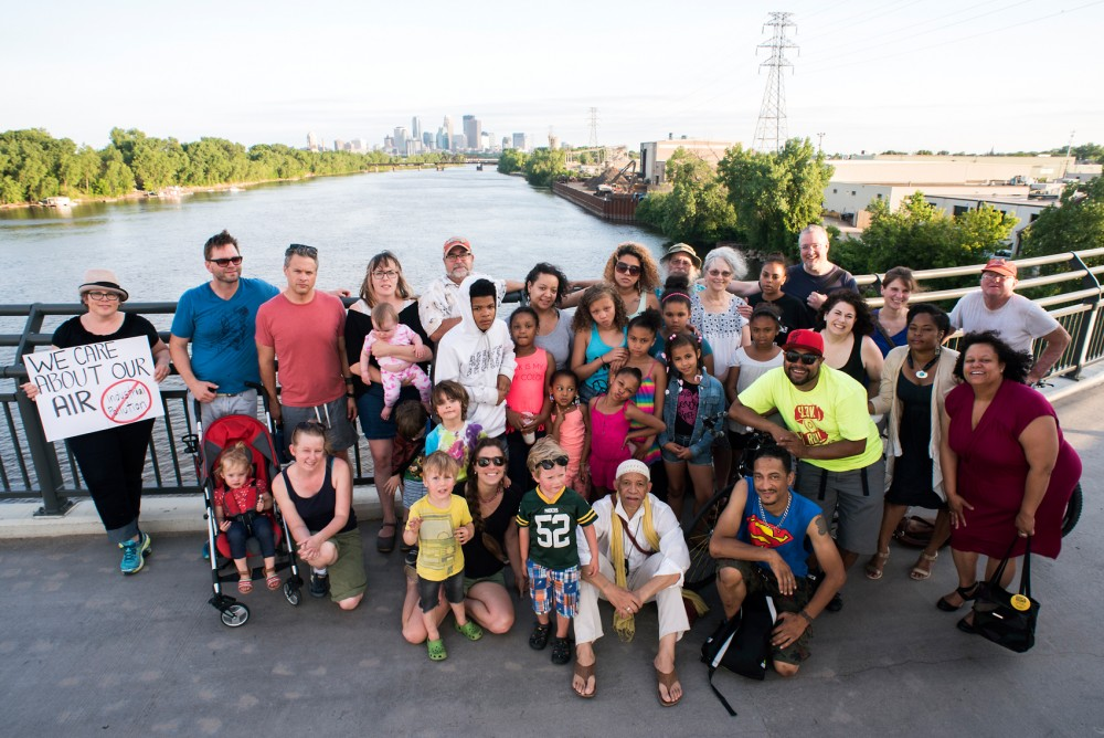 Members of the North Minneapolis community come together on the Lowry Avenue Bridge in unity against Northern Metal Recycling, as seen in the distance behind them on the evening of June 9. A report by the Minnesota Pollution Control Agency that lists the neighborhood surrounding the facility as the city's highest levels of lead poising and asthma hospitalizations, and points to the recycling facility as a leading cause in the issue.