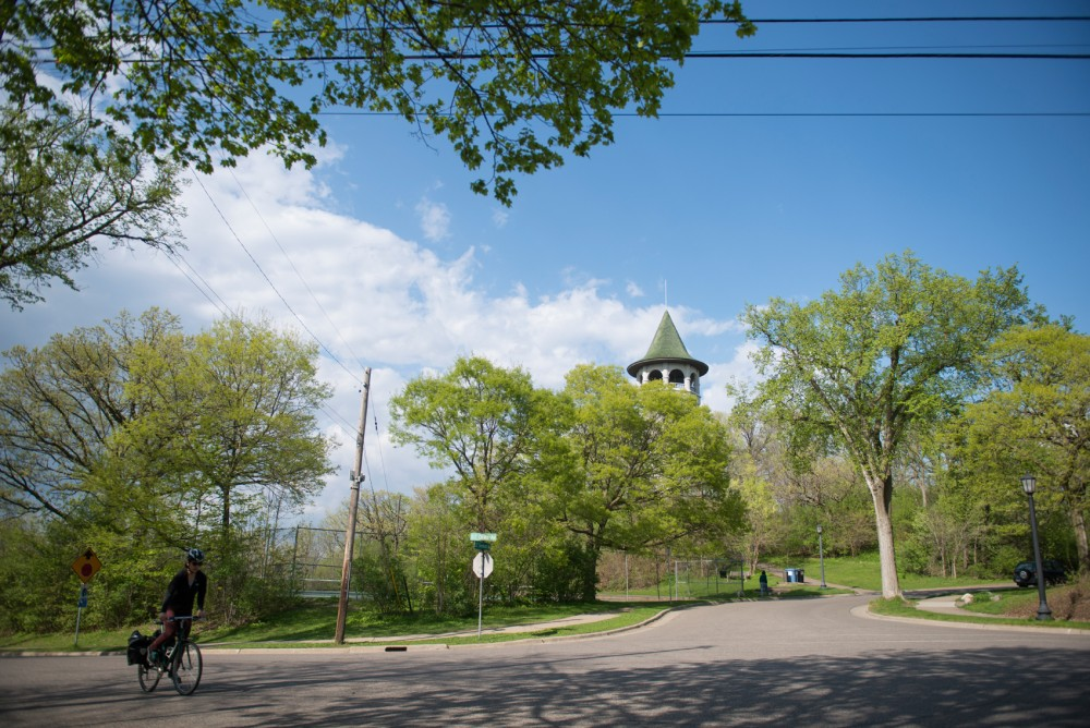 A woman bikes past the witchs tower on southeast Orlin avenue  Tuesday Afternoon. Although about half of the neighborhood is made up of students, currently no student is part of the Prospect Park Association.