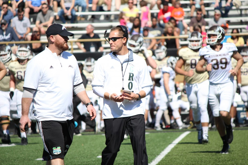 P.J. Fleck (middle) speaks with a coach during a Western Michigan game. Fleck went 13-1 in his fourth and final season with the Broncos in 2016.