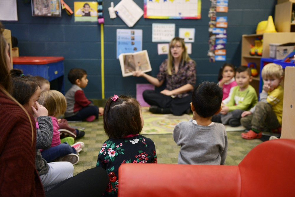 Children sit and listen as they are read a story at the Community Child Care Center on Monday, Jan. 30, 2017 in St. Paul. The daycare's funding from student service fees has been cut over 70 percent.