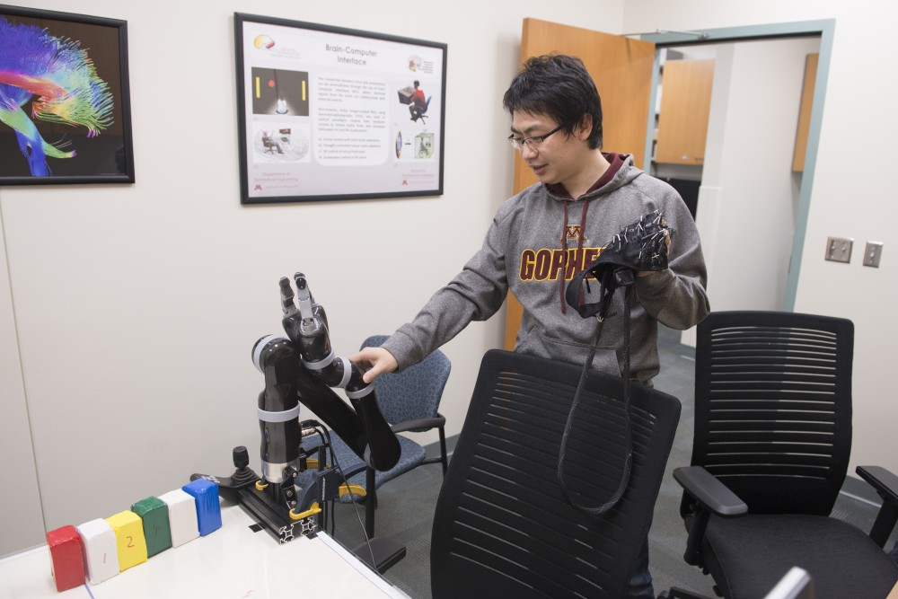 Biomedical engineering postdoctoral researcher Jianjun Meng explains how a sensor cap detects brain signals that move a robotic arm in Nils Hasselmo Hall on Monday, Jan. 30, 2017.