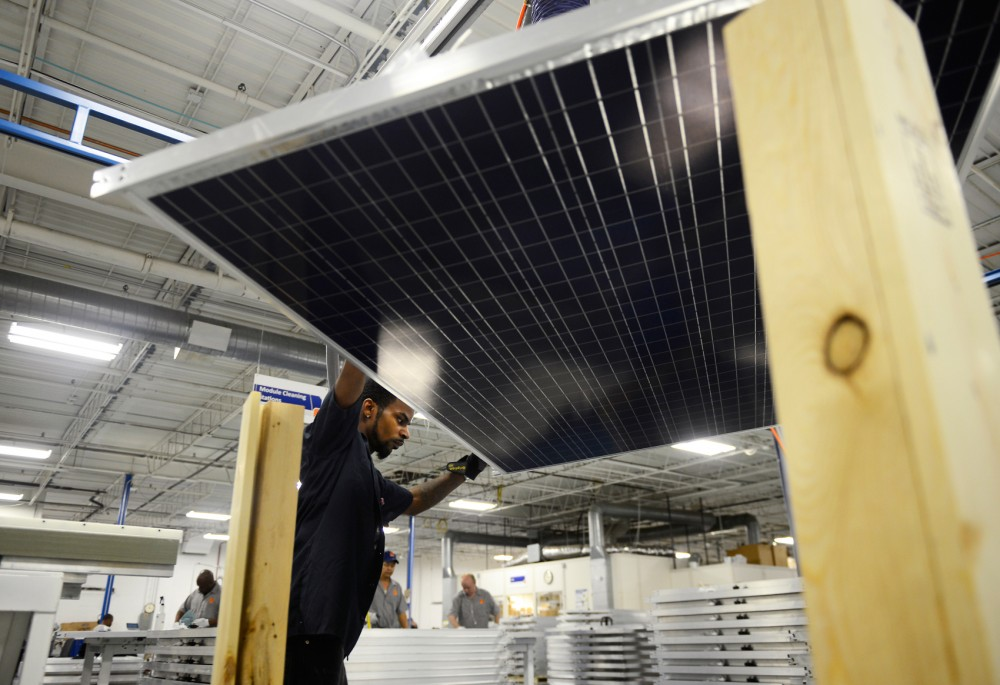 Employee of tenKsolar, Dwayne Blakely, moves solar panels onto a module light table for testing on Jan. 25, 2016. The University of Minnesota will be installing solar panels in an effort to make progress on a climate action plan.