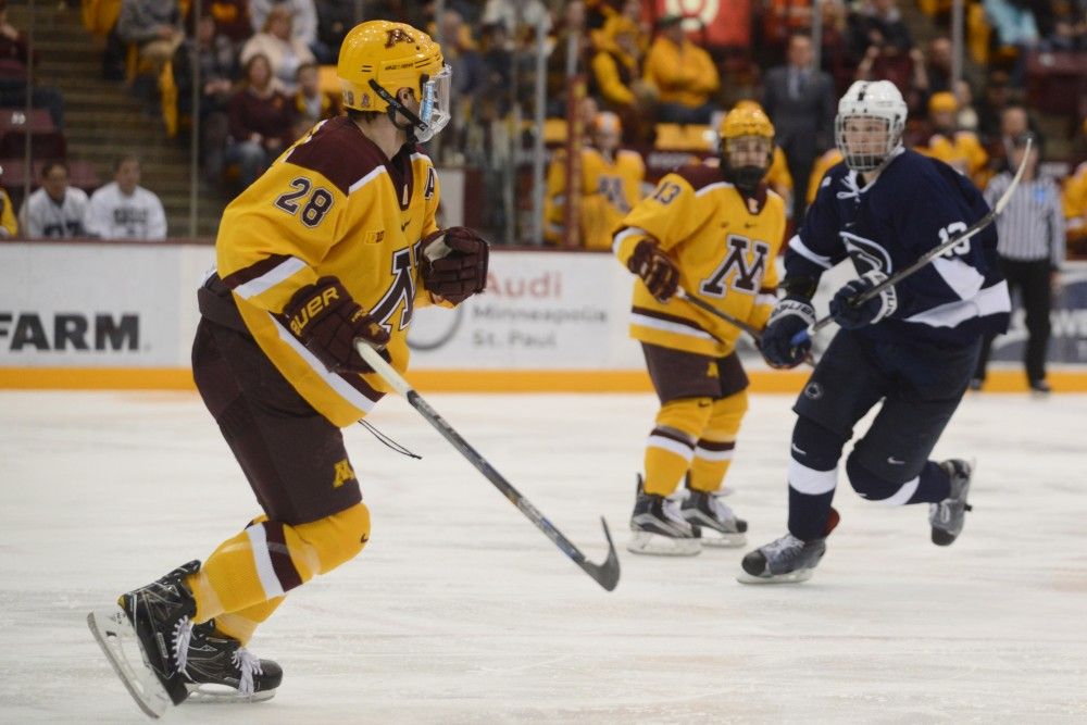 Jake Bischoff, left, eyes the puck at Mariucci Arena in Minneapolis on Friday, Feb. 4, 2017. The Gophers beat Penn State 5-2 for their sixth consecutive win.