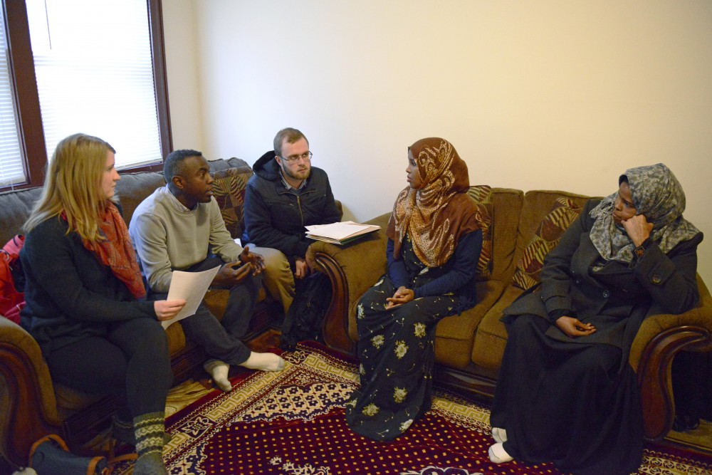 Somali refugee Hodan Mursal, right, works with members of the Refugee Resettlement Program to complete paperwork to formally settle her into her new home in South Minneapolis on Friday, Feb. 10, 2017.