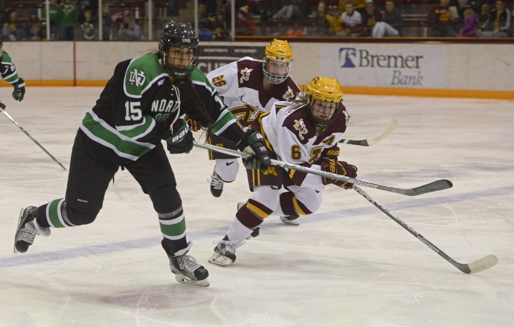 Kate Schipper, front, and Sarah Potomak, back, chase the puck on Friday, Feb. 10, 2017 at Ridder Arena in Minneapolis. The gopher women's hockey team won against UND 4 to 2.