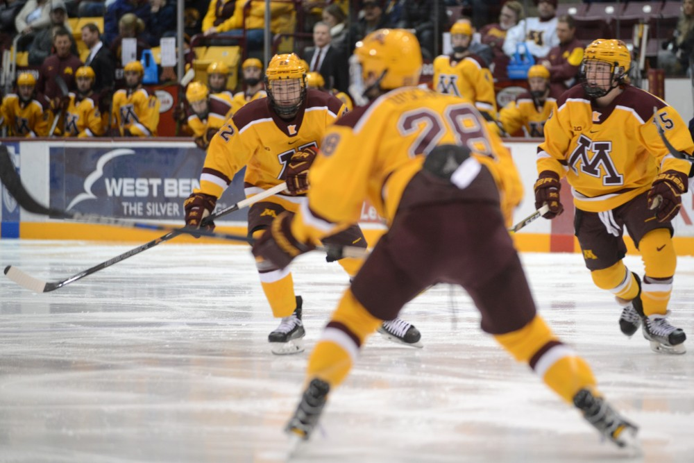 Tyler Sheehy, left, and Rem Pitlick, right, watch a play unfold at Mariucci Arena on Feb. 4.