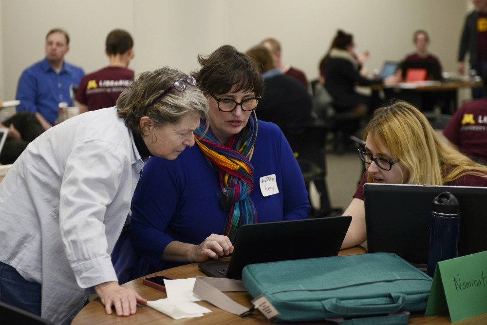 Shannon Farrell, a University staff member, works with Kathy Shipp, center, and Maria Fitzgerald, left, during the DataRescue event on Friday, Feb. 24, 2017 at the Humphrey School  School of Public Affairs.