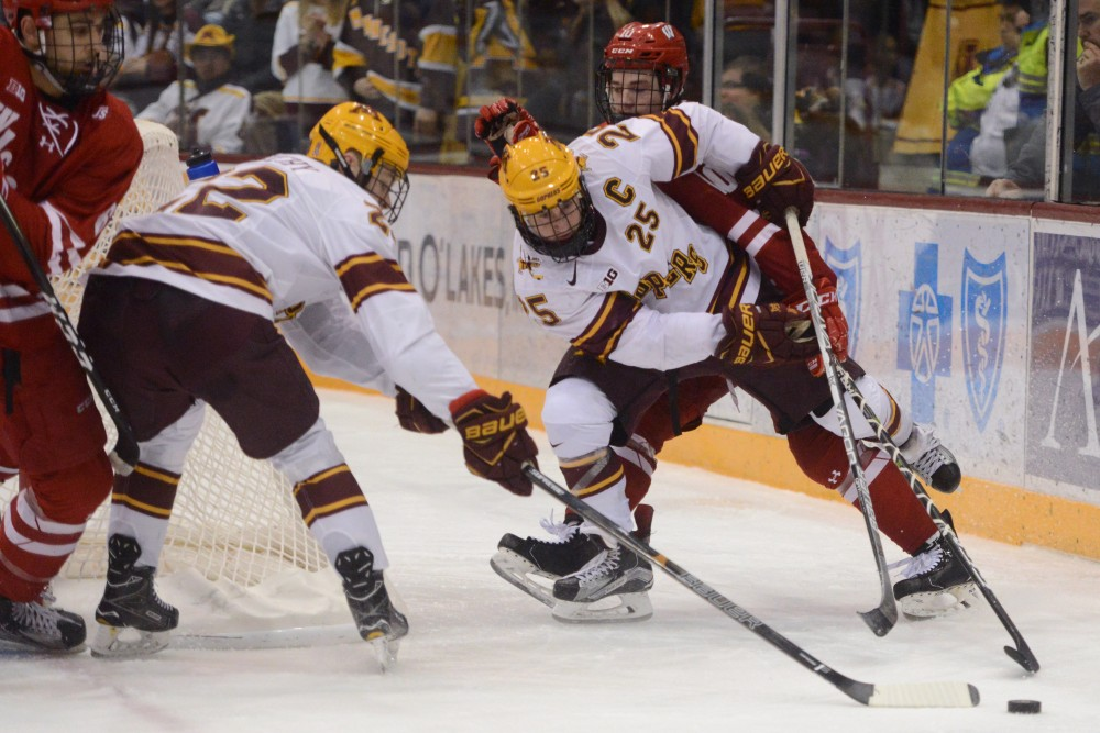 Gophers forwards Justin Kloosand Tyler Sheehy fight for the puck against Wisconsin on Saturday, Feb. 25, 2017 at Mariucci Arena.