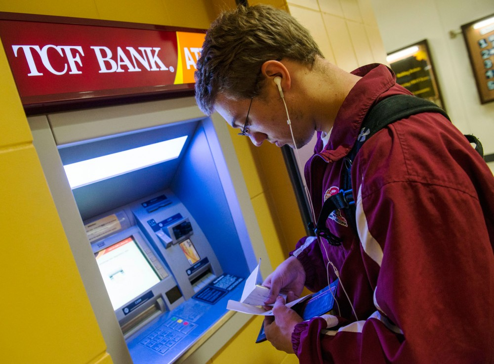 Economics sophomore Alex Carlson uses the ATM outside TCF Bank in Coffman Union to deposit a check Tuesday, Sept. 10, 2013.