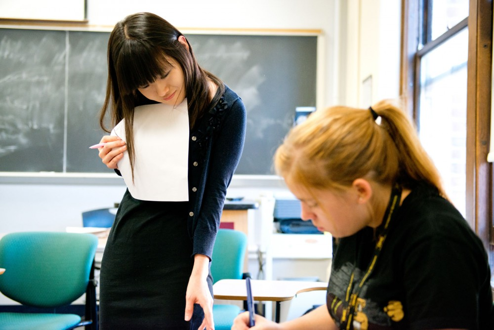 Instructor Hyeryung Hwang helps a student during a group discussion in a University writing class in Lind Hall.