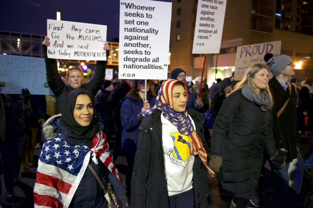 Iraqi refugees Hawra Albattat and Saja Alnabi march through downtown Minneapolis to protest President Donald Trump's immigration ban on Tuesday, Jan. 31, 2017.