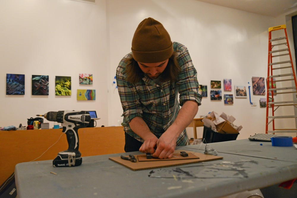 Miles Taylor prepares the back of a piece of artwork to be displayed at the Gamut gallery in Minneapolis on Tuesday. The 2017 Minneapolis installment will feature an exhibition of more than 90 artists from around the world running March 11-31.