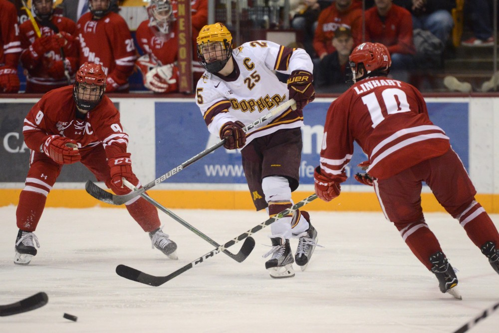 Senior forward Justin Kloospasses the puck up the ice against Wisconsin on Saturday, Feb. 25, 2017 at Mariucci Arena.