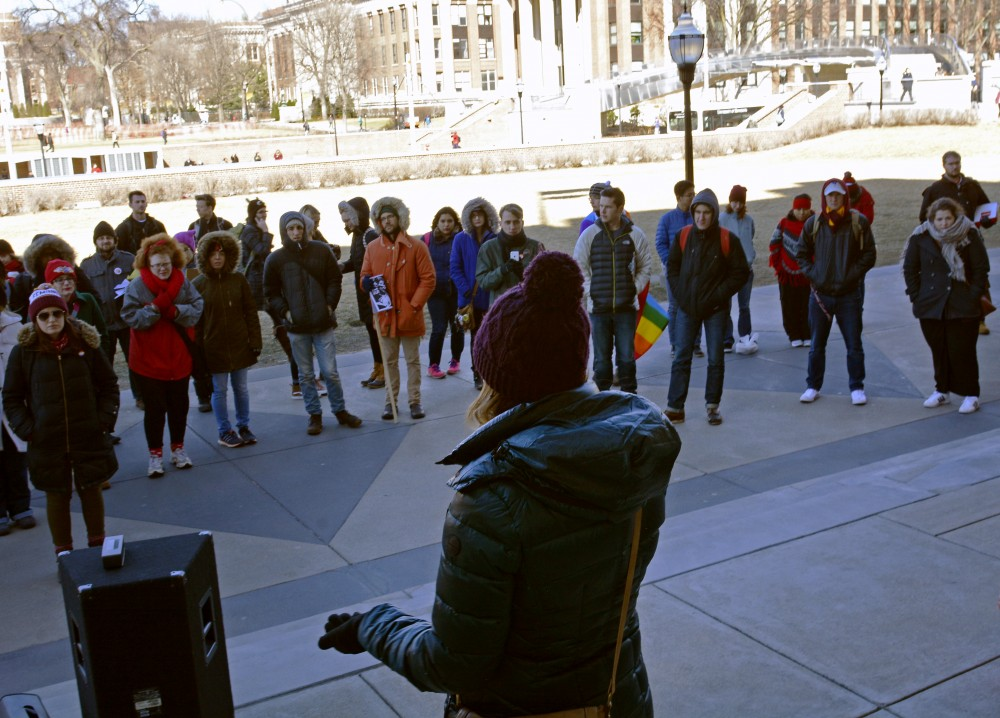 A student speaks to the crowd outside of Coffman Memorial Union during the Student Day of Action for International Women's Day on Wednesday, March 8, 2017.
