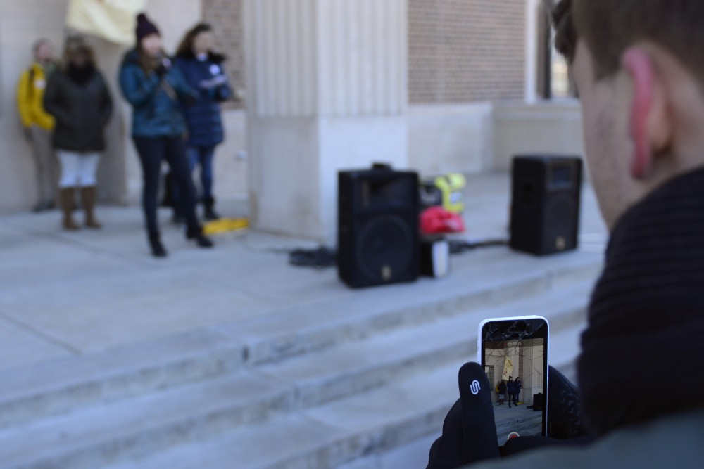 Tyler Vasseur of Socialist Alternative Club takes a video of a speaker during the Student Day of Action for International Women's Day on Wednesday, March 8, 2017.