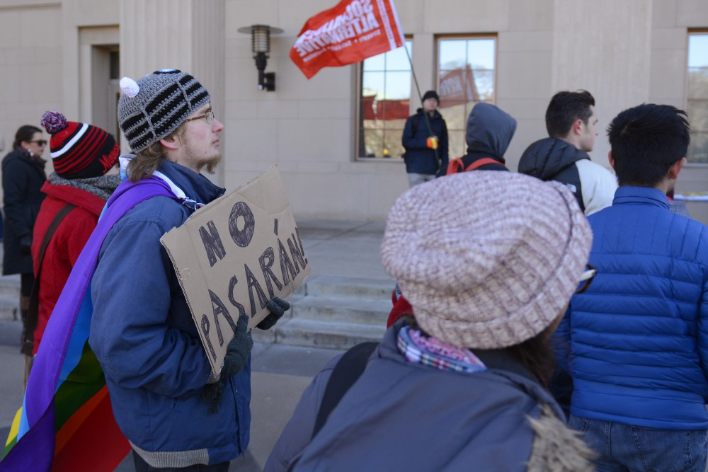 Augsburg College student Kelton Holsen holds a sign which translates to