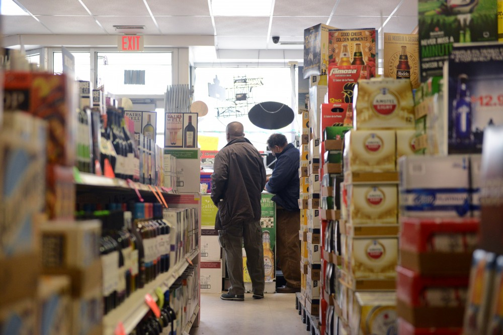 Two men work inside the store at Cedar Riverside Liquor on Monday, March 20, 2017.