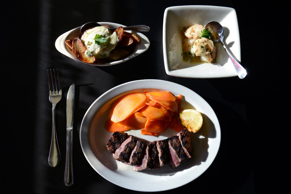 A 10 ounce New York Strip with grilled lemon and poached carrots beside a side of shrimp scampi and Potatoes Confit with chive mascarpone at The Strip Club Meat & Fish in St Paul.