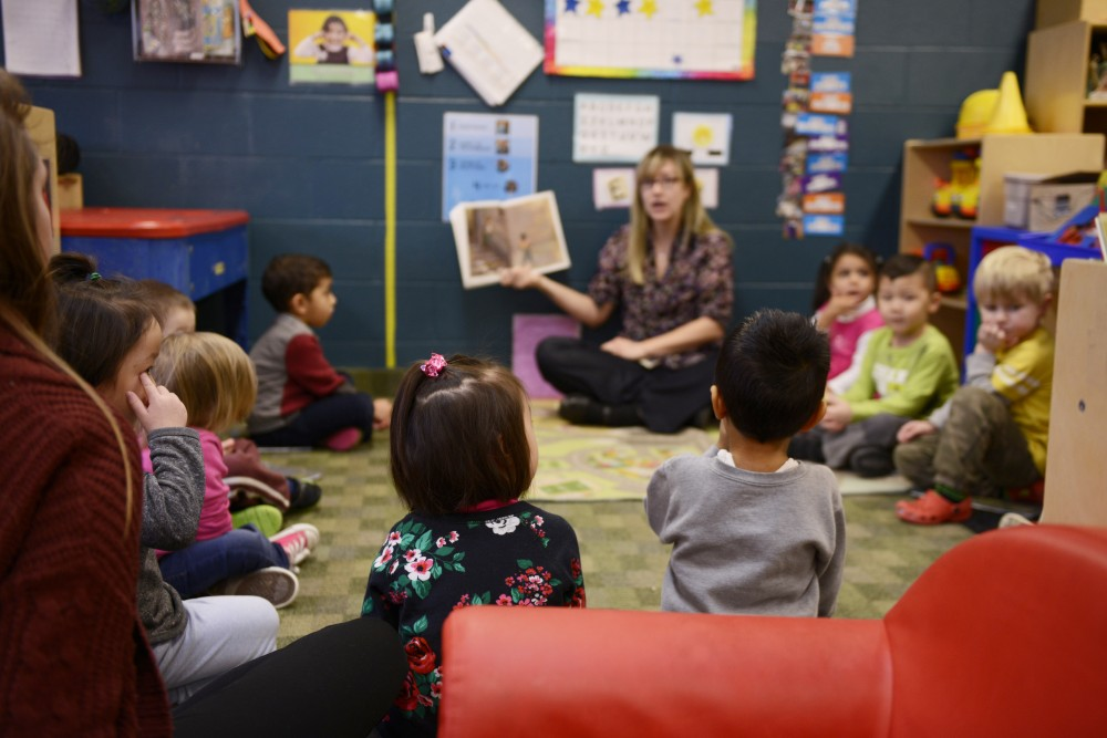 Children sit and listen as they are read a story at the Community Child Care Center on Monday, Jan. 30, 2017 in St. Paul. The Council of Graduate Students  passed a resolution March 20 to symbolically support the daycares, which could lose more than $30,000 in funding due to a new student service fees allocation process.