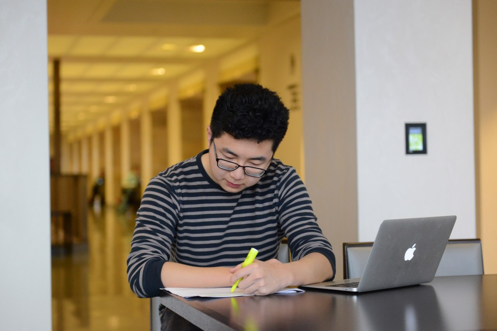 PSEO student Andrew Yang studies before class in Northrop Auditorium on Friday, March 24, 2017.
