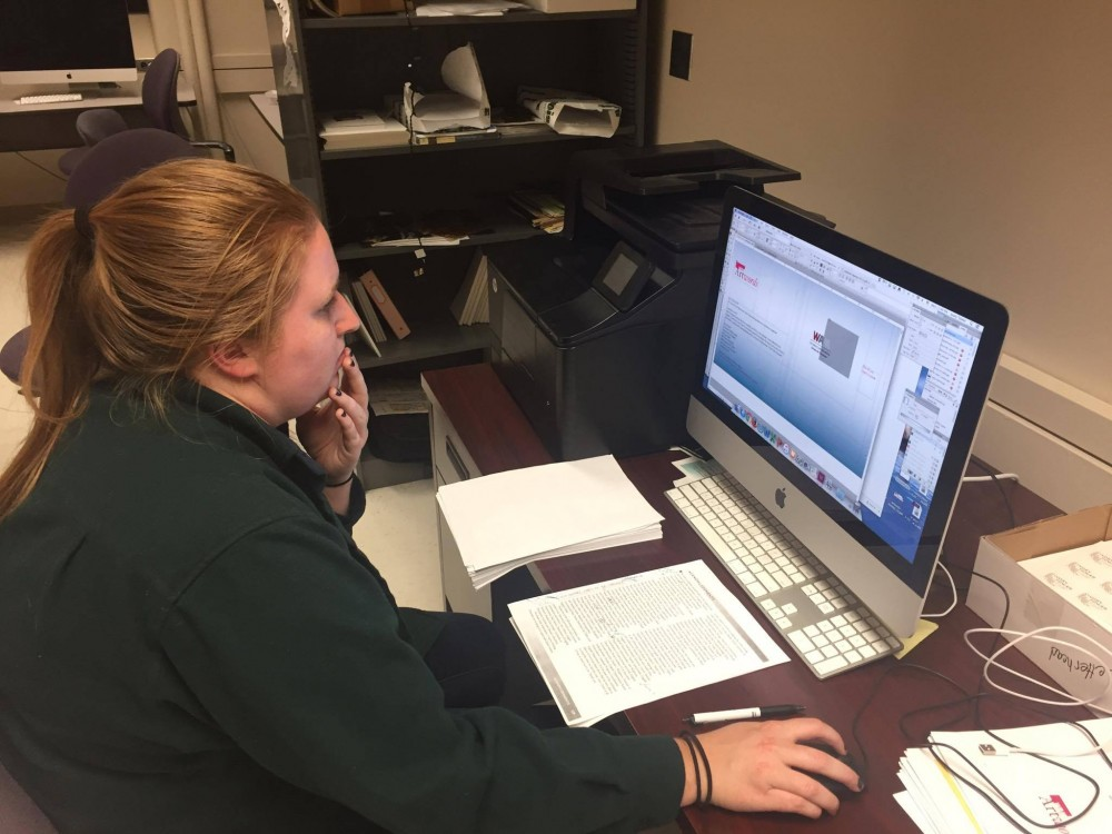 <p>Maggie Benson, Ivory Tower's design manager, makes finishing touches on a design in Lind Hall on Wednesday, March 22. </p>