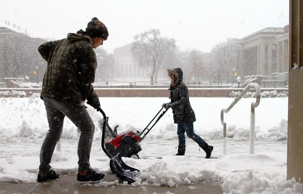 Students shovel snow outside Coffman Unionon Dec. 13, 2010.For the last 18 months, Minnesota has seen above average temperatures.