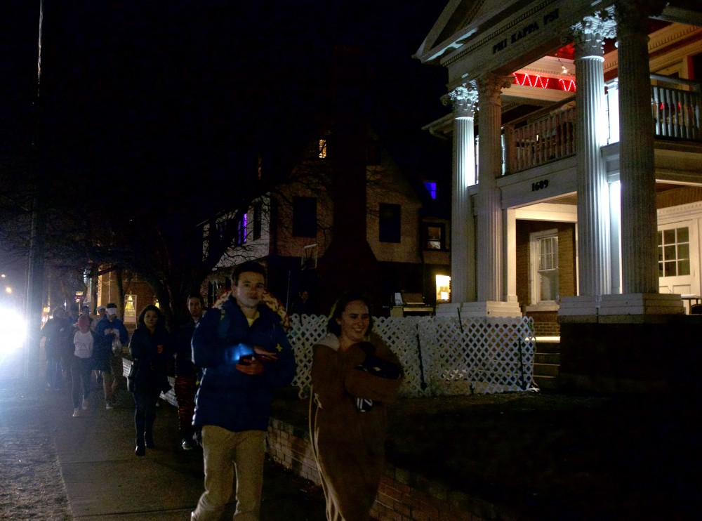 A large group of students walk past fraternities on Fraternity Row on March 10, 2017.