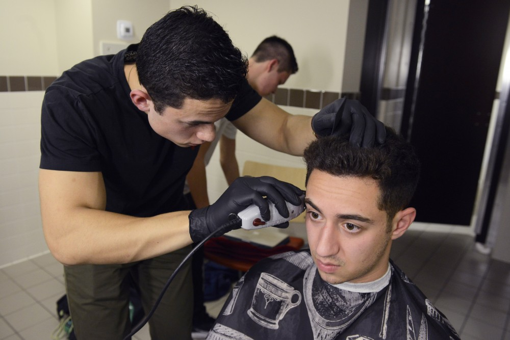Adam Mikell works on a haircut for one of his frequent customers, Adi Mizrahi, on Thursday, March 6, 2017 in the 17th Avenue Residence Hall.