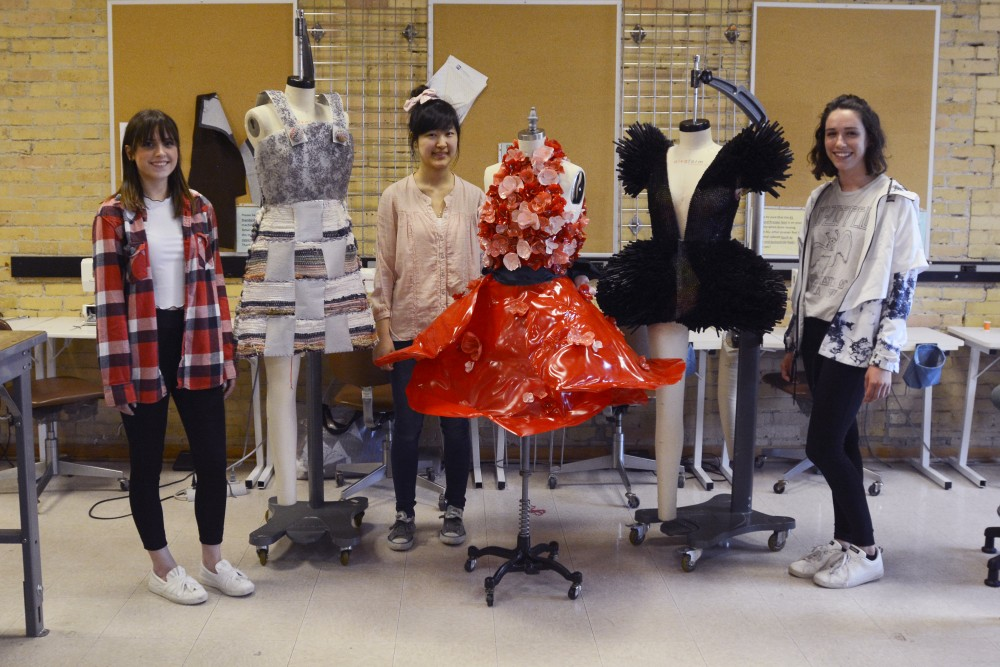 Apparel design sophomores Hailey Strobel, left, Stephanie Wang, center, and Karli Rastetter, right, pose for a portrait with their pieces at their studio in McNeal Hall on Tuesday, April 18, 2017. Their work will be showcased in IMPRINTS at the Weisman Art Center on Wednesday, April 19, 2017.