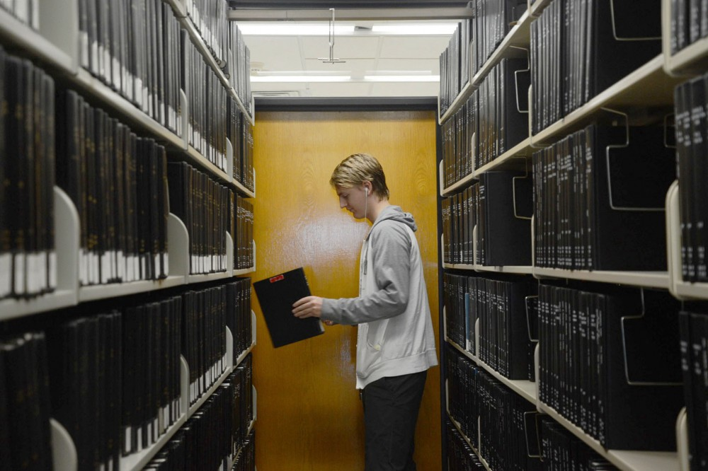 Marketing major Ben Sundem pulls books from Wilson Library on April 21, 2015. A $60 million update is planned for the building, with the project currently in the pre-design phase.