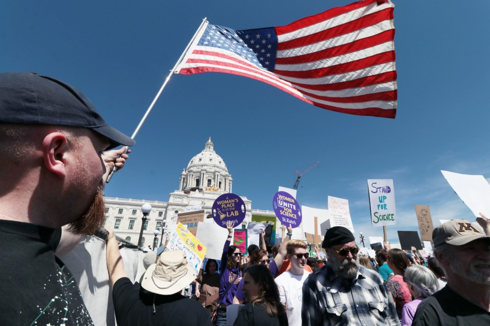 Ecolab chemical engineering teacher Nathan Thompson holds the American flag as additional protesters raise their signs on Saturday, April 22, 2017 in St. Paul. Thousands marched in solidarity across the nation to promote funding for scientific research.