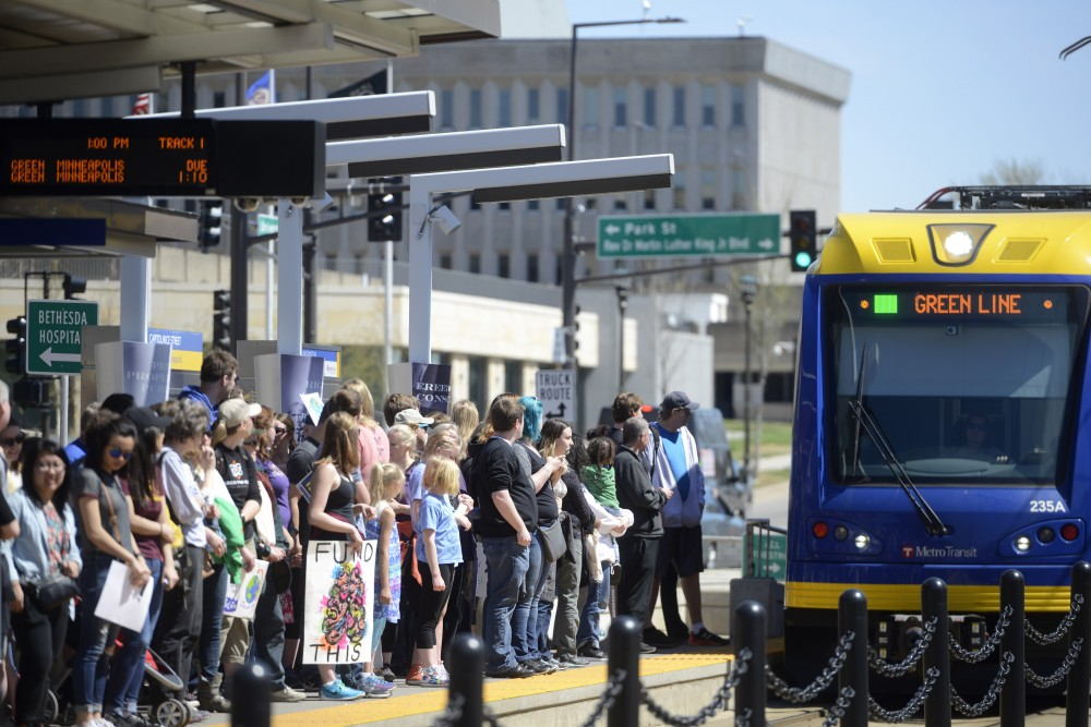 After the March for Science on Saturday, Apr. 22, 2017 in St. Paul, protesters wait for a west bound green line light rail.