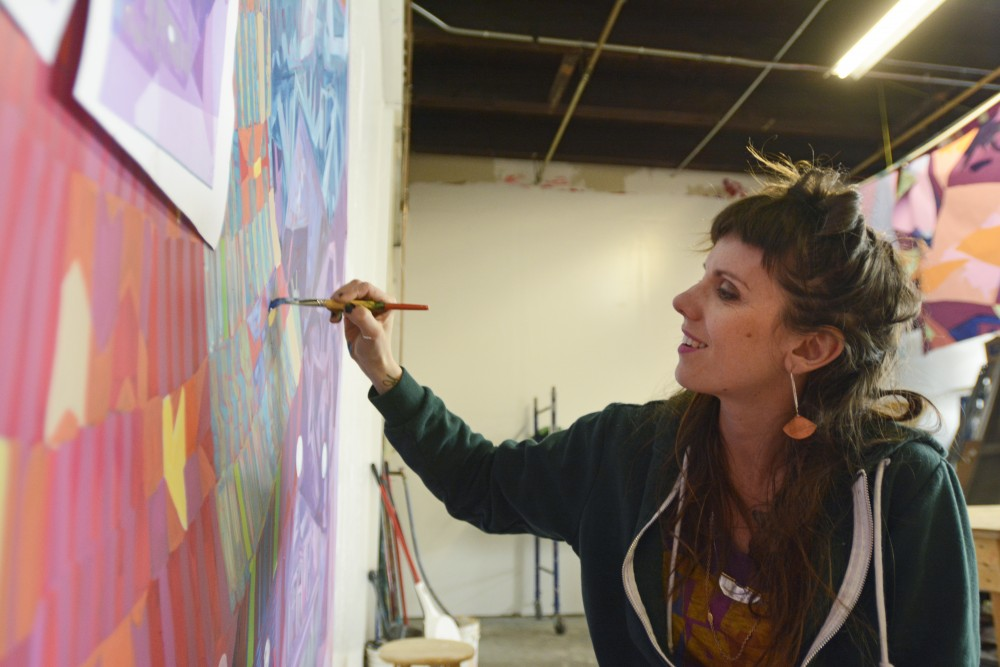 Greta McClain, lead artist of GoodSpace Murals, paints a new project for The John & Denise Graves Foundation on Tuesday, April 25, 2017 in Minneapolis. The muralist group works mostly with schools and non-profit organizations to bring art into the community, including the University's HECUA program.