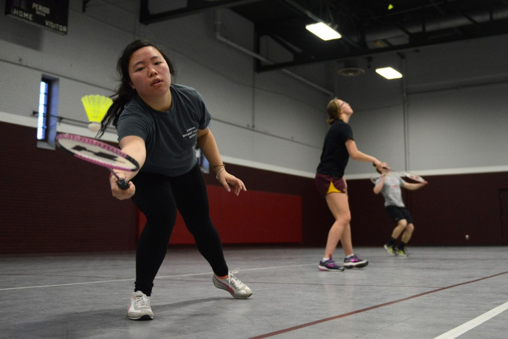 Sociology major Victoria Lee, whos been playing the game for six years, reaches for the birdie during a match of badminton in Cooke hall.