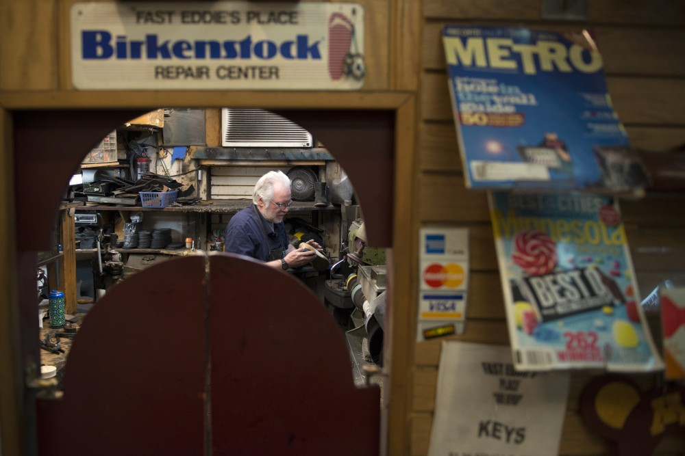 Owner of Fast Eddies Place Jim Picard sands the sole of a shoe inside his repair shop in the Dinkydale building.
