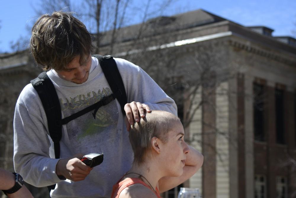 Cival Engineering sophomore Thomas Calhoon shaves Art Education junior Kourtney Culver's head in front of Northrup Auditorium.