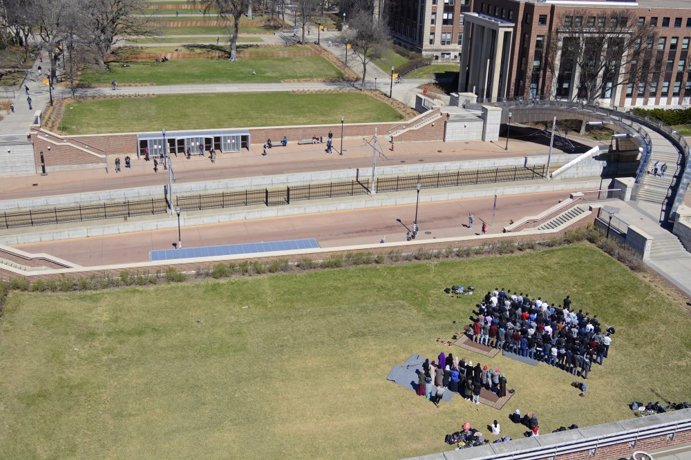 A muslim prayer service is held in front of Coffman Memorial Union.